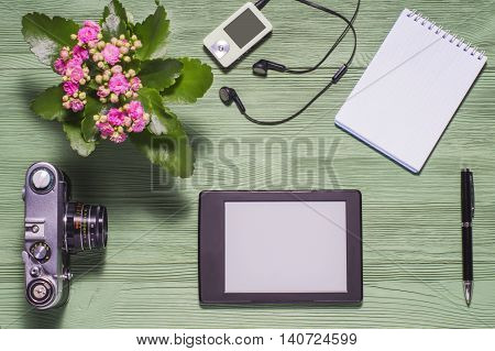 Flat lay of personal stuff tablet pc camera photonotebook and other. Flat design and top view on green wooden background. Mockup consisting of tablet pc in landscape orientation and blank notebook.