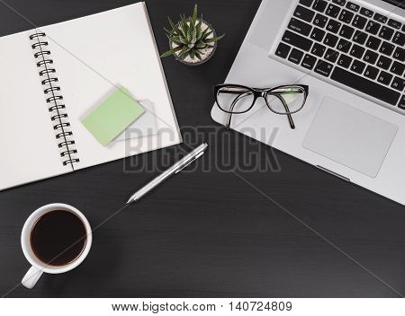 Business's desk with other equipment Tools and Notebook.Top view on opened notebooksticky note cup of coffee and clock on black wooden office desk.with copy space