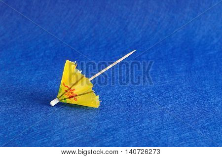 A yellow cocktail umbrella isolated on a blue background