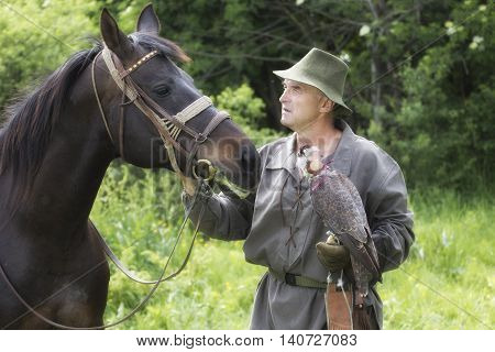Hawker in traditional clothing with peregrine falcon and horse