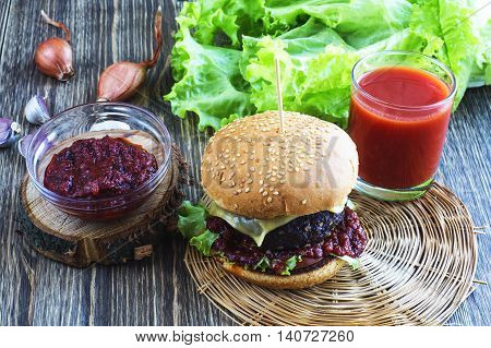 Delicious burger with beef tomato cheese and lettuce. Homemade hamburgers with fresh vegetables and a glass of tomato juice