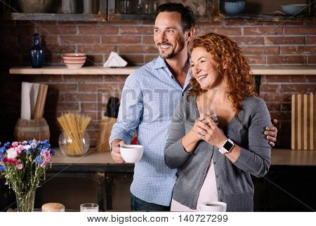 Look there. Extremely happy husband and wife looking aside while holding a cup of coffee and standing in the kitchen