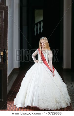 small girl kid with long blonde hair and pretty happy smiling face in prom princess white dress and red miss ribbon with crown on head