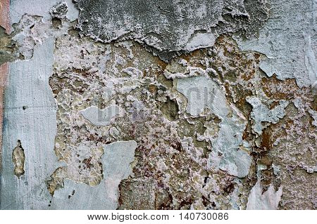 Peeling multi-layer painted wall of the house