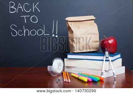Back to school school books with apple and paper bag lunch on desk