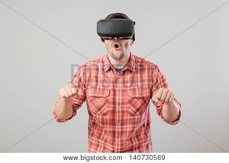 Attractive man with virtual reality glasses paying bike simulator isolated on a gray background