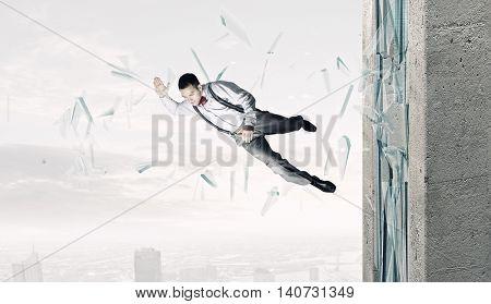 Man breaking through glass . Mixed media