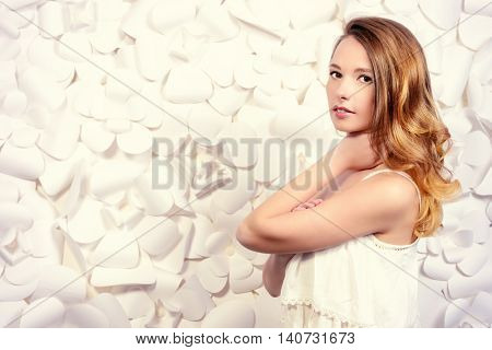 Spring portrait of a beautiful young woman over white floral background. Beauty, fashion, cosmetics.