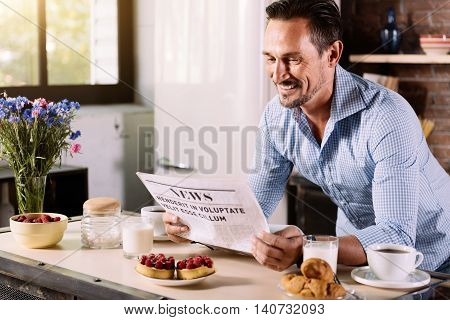 Lets get some news. Contented bearded middle aged man reclining on the table with breakfast and reading a newspaper in the kitchen