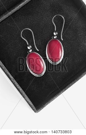Red garnet earrings in black opened jewel box closeup