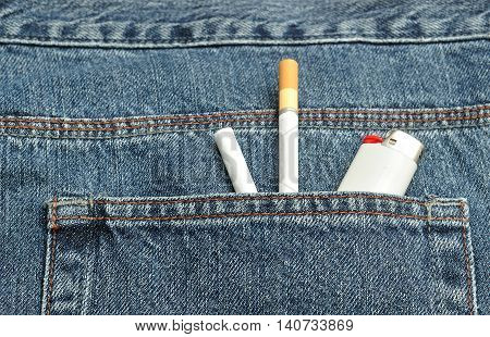 Two cigarettes with a lighter in the back pocket of a denim jeans pants