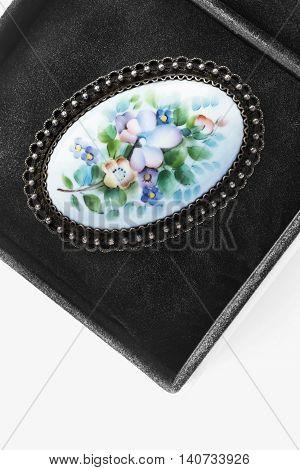 Vintage painted brooch in black jewel box closeup