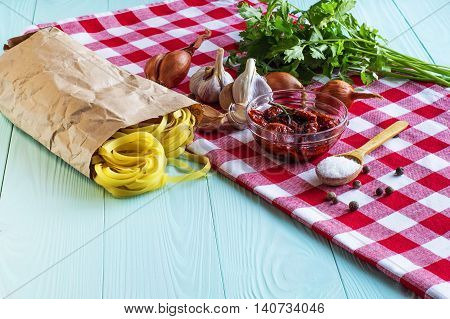 Italian food cooking ingredients. Pasta sun-dried tomatoes onions garlic spices salt in the wooden background.