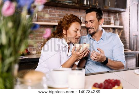 As sweet as sugar. Fantastic middle aged woman holding a bowl with strawberries and smelling it while her husband looking at her