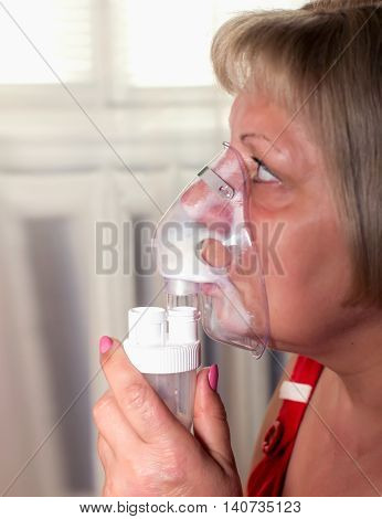 woman breathes with an inhaler the treatment of colds and coughs a soft focus on the eyes selective focus