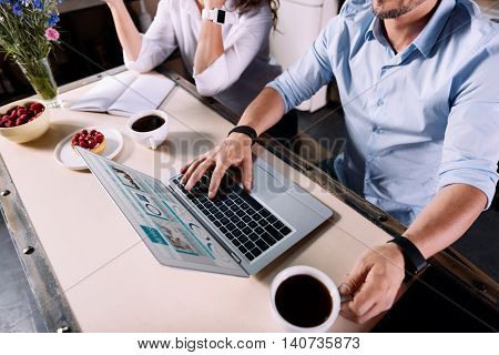 Some time for work. Top view of hands of a man reading news on the computer at the table in the kitchen while his wife sitting near him and talking on phone