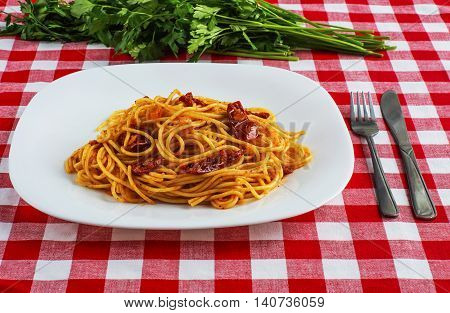 Spaghetti with tomato sauce and parsley on on red-white tablecloth. Pasta with sun-dried tomatoes.
