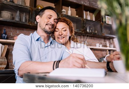 For not forget. Pleasant middle aged couple sitting in their kitchen and making a list of purchases