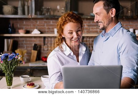 It is funny. Cheerful woman laughing while looking at the laptop and standing near a man who smiling and looking at her in the kitchen