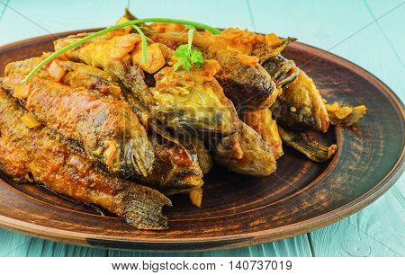 Fried fish gobies in tomato sauce on a ceramic plate on a blue wooden background. Fish breed bull.