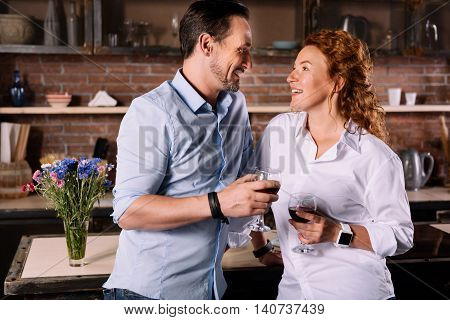 After work. Gorgeous middle aged woman looking at her handsome smiling man while drinking wine in the kitchen