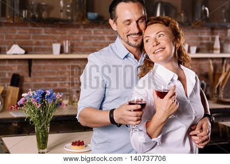 You are my precious. Contented mature man hugging an energetic woman from the back while drinking wine in the kitchen
