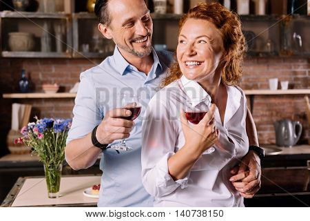 You are so cool wife. Joyful bearded man hugging an enthusiastic woman from the back and looking at her while drinking wine in the kitchen