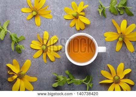 Cup of tea with yellow flower on stone background