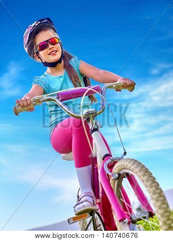Girl bicycling child. Girl child rides bicycle. Little girl in cycling. Bicycling is good for child health. Cyclist look away. Bottom view.