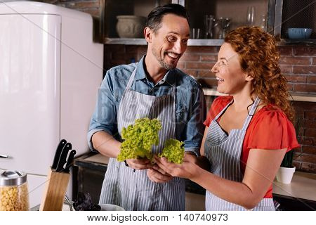 So nice to do it with you. Ecstatic bearded man smiling and looking at contented woman while holding leaves of a salad