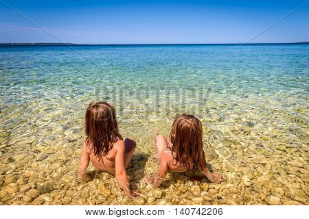 Children on Beach in Croatia island Pag or Hvar. Twins sitting in Turquoise and blue sea water of Adriatic and Mediterranean sea. Beautiful background landscape photo with calm sea water and blue skies.