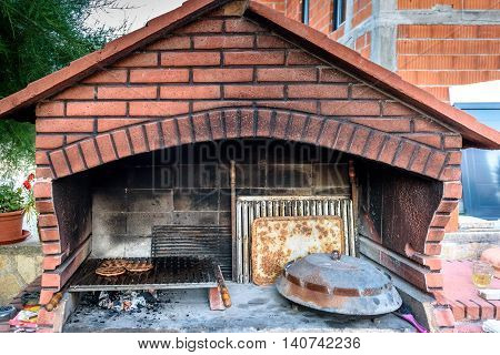 Making Burgers In Big Barbecue Grill Fireplace With Different Accessories.