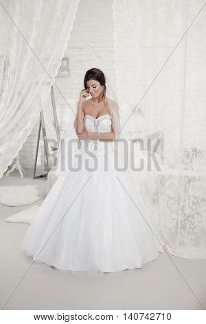 Beautiful bride standing in bedroom in wedding dress. Full size.