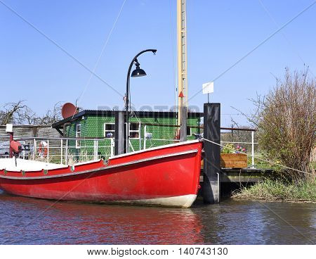 Anchored motorboat on a jetty. Wooden jetty or pier with red boat anchored. Sunny day with clear blue sky.