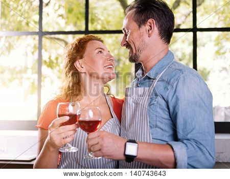 Unforgettable evening. Charming woman and handsome man looking at each other with love while clinking wine glasses in the kitchen