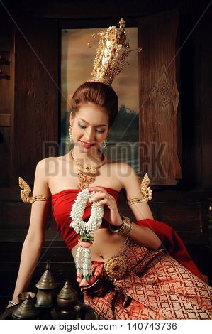 Thai woman dressing traditional costume sit next to window hold flower floral in thai old house style.