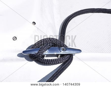 Anchored boat. Close-up of a moored motorboat or sailing ship. Rope fixed on a yacht.