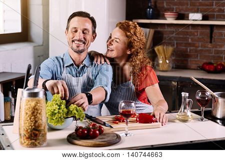 Helpful husband. Tender woman touching a shoulder of her husband who helping her to cook