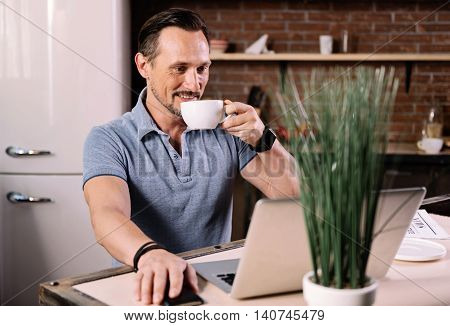 Very interesting. Good looking mature man looking at the screen of the laptop with interest while sitting at the in the kitchen