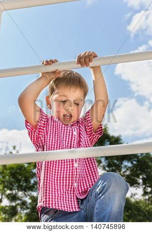 Boy climbs up on a ladder a bottom view in the open air against the blue of the sky