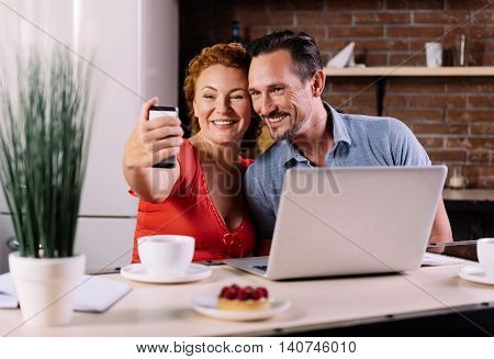 Let me take a selfie. Contented mature man and an energetic woman taking a selfie while sitting at the table in their kitchen