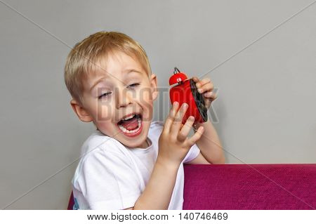 Boy Holding An Alarm Clock, A Child And Time Red, Concept Of Time, Focus On The Alarm Clock