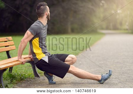 Young Man Doing Stretching Exercises On A Bench