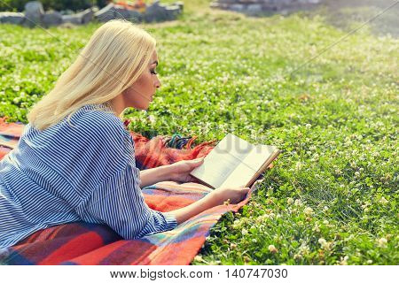 Young teen girl read book and study homework outdoor in nature with green grass on background. Girl reading a book lying in meadow grass. View from the back of a girl reading a book.