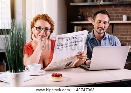 Be aware. Relaxed middle aged woman with glasses reading a newspaper while her husband using a laptop in the kitchen