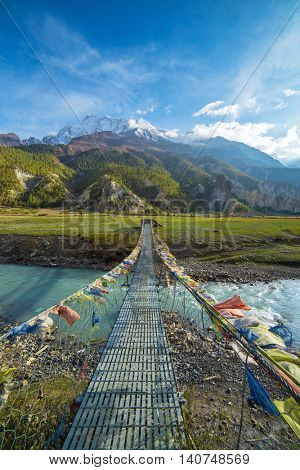 Suspension bridge with buddhist prayer flags on the Annapurna circuit trek in Nepal