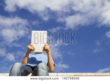 Boy with tablet PC against blue sky. Childhood technology leisure concept