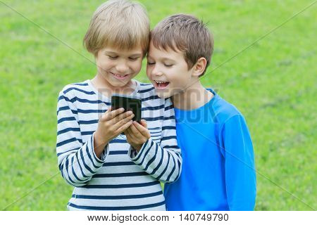 Children with smartphone. Boys smiling looking to phone playing games or using application. Outdoor. Technology education leisure people concept