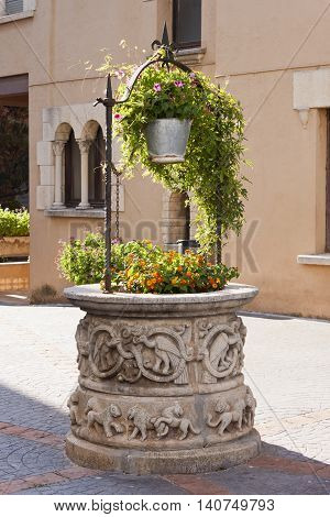 Antique sculpted stone water well and bucket with flower plants decorations in Roc de Sant Gaieta Tarragona Spain.