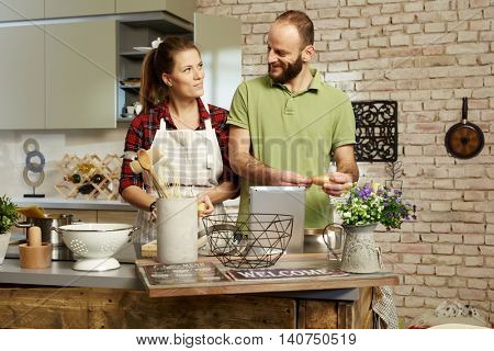 Young loving couple cooking together at home in kitchen.